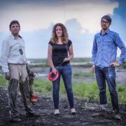 three faculty standing in a field for research