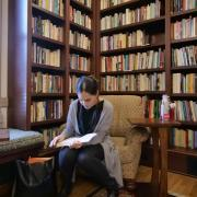 student in book-lined library