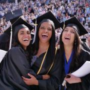 three students celebrate graduation