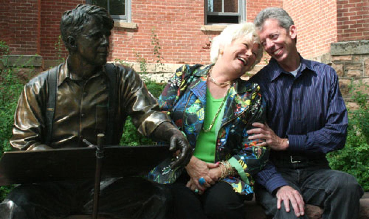 Roe Green and Bud Coleman share a laugh next to a statue of Robert Frost on the CU-Boulder campus.