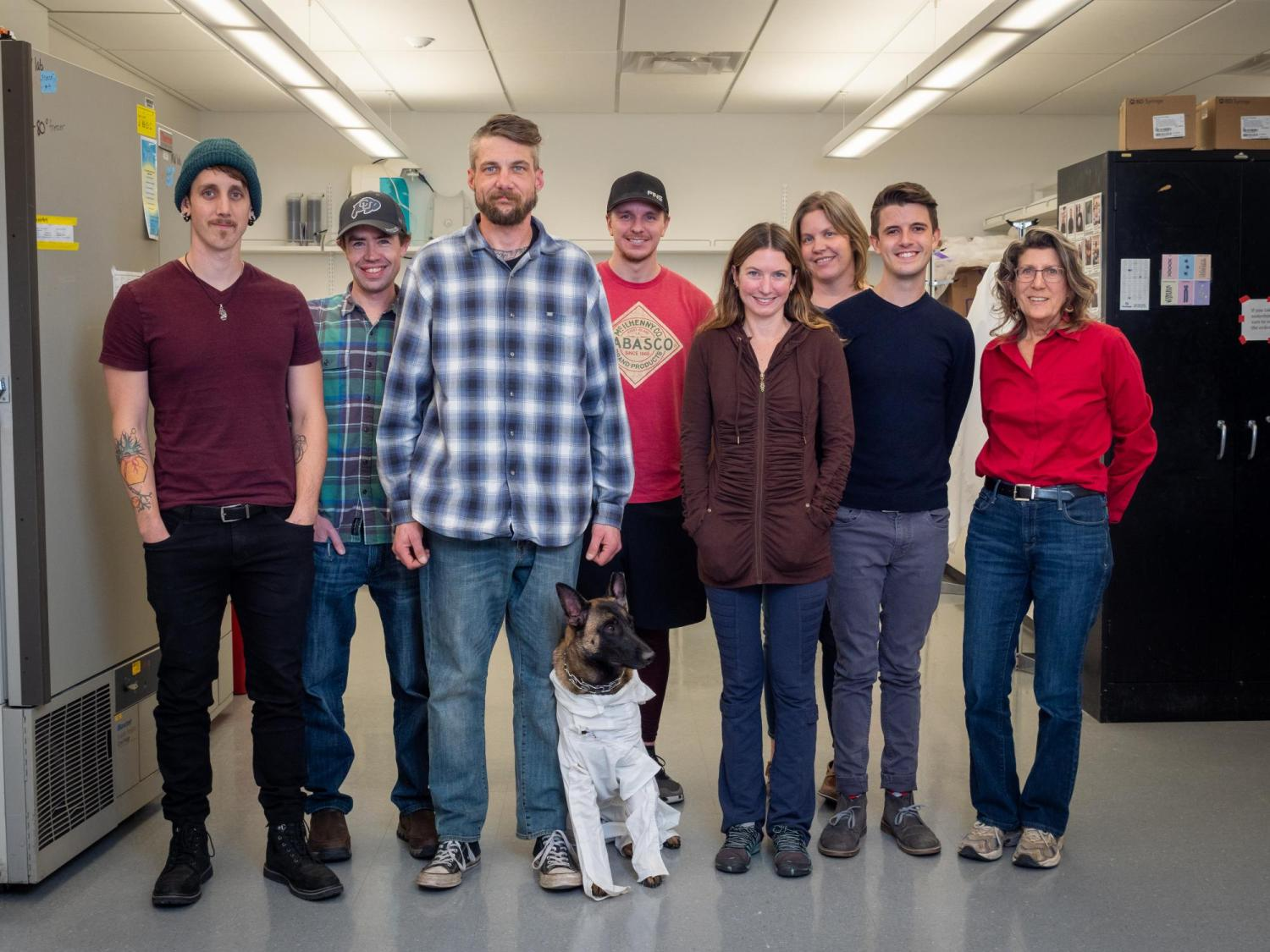 Dr. Watkins and her team in the lab with Navy veteran Jon Coulson and his service dog Xenna.