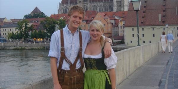 Alums Alex Becker and Kristen Allen don traditional Bavarian clothes with the Regensburg Dom behind them. Photo courtesy of Alex Becker.