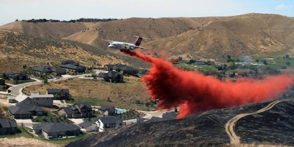 Plan flying putting out fires by a neighborhood