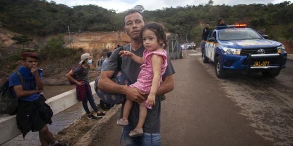 Migrants hoping to reach the distant U.S. border walk along a highway in Guatemala in January 2021. AP Photo/Sandra Sebastian