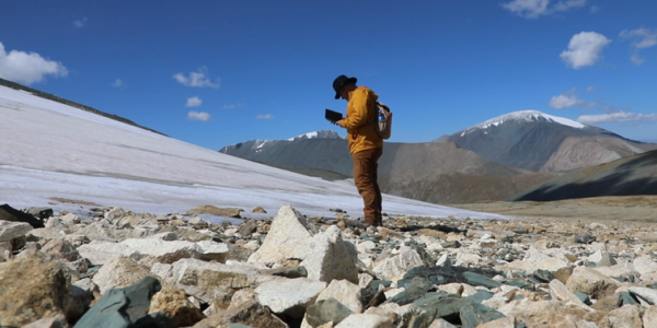 Archaeologist and paleoenvironmental researcher Isaac Hart of the University of Utah surveys a melting ice patch in western Mongolia. Peter Bittner, CC BY-ND