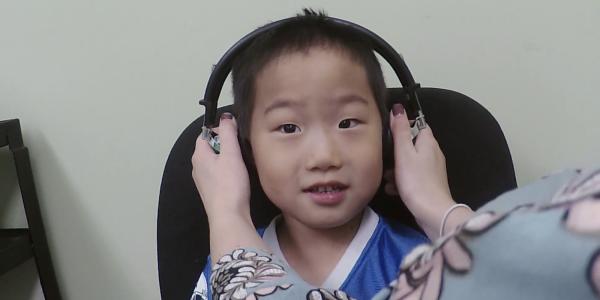 Child getting headphones put on their head