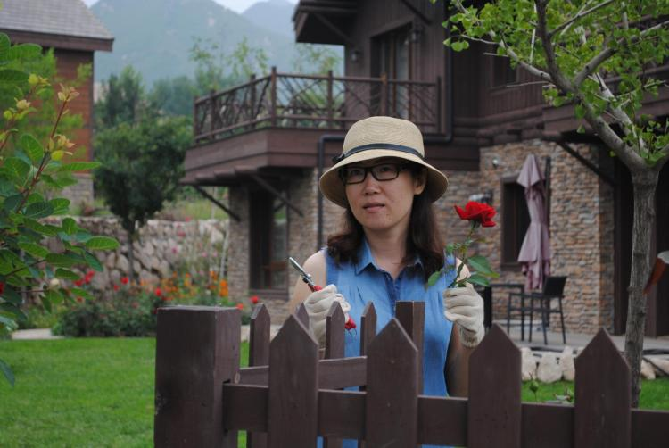 Annie Liu outside her home with a rose