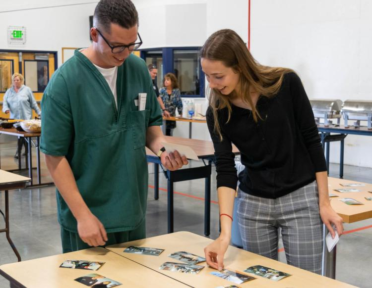 Photograph of an inside student and outside student looking at photographs