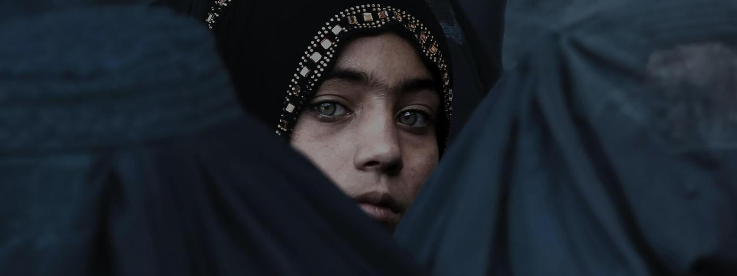 Afghani woman looking through a crowd