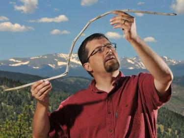 Craig Lee, of the University of Colorado Boulder, holds a 10,000-year-old atlatl dart that had been frozen in an ice sheet near Yellowstone National Park. The dart was straight when it was entombed and became bowed from the melting and barely survived being snapped in half by a passing animal. Credit Casey A. Cass/University of Colorado.