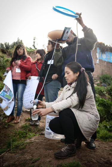 Katheryne Rosa Barazorda Cuellar, kneeling, demonstrates a water filter that rural Peruvians can use to get safe, affordable drinking water.