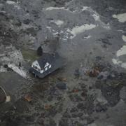 A house is shown surrounded by coal fly ash after a retention pond near Kingston Fossil Plant in Tennessee overflowed.