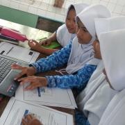 Four young girls use the PhET simulations in Indonesia.