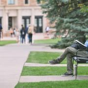 Man sitting on a bench on campus