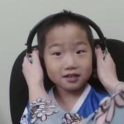 Child getting headphones put on their head