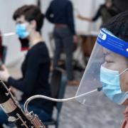 A musician playing an instrument through a faceshield