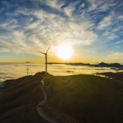Stock photograph of a wind turbine at sunset