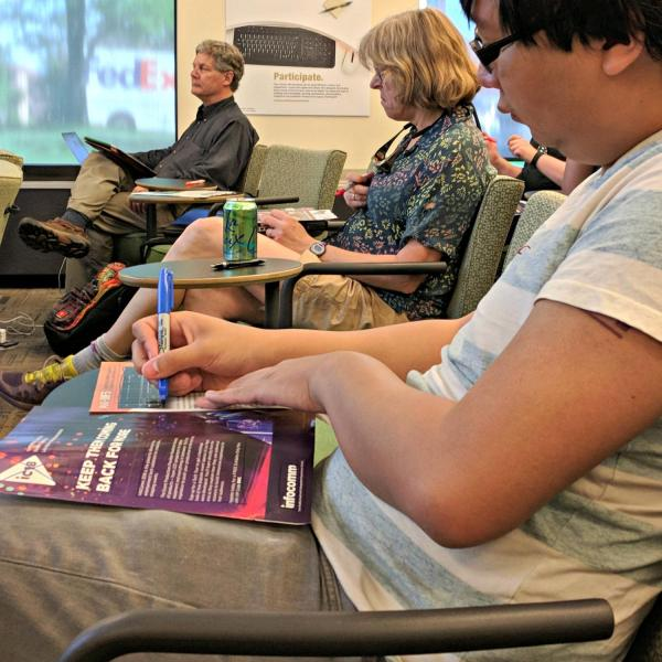 Austin Chau marking up magazine pages in a workshop on graphic design