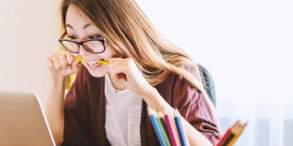 Student working at a computer and biting down on her pencil with an anxious expression