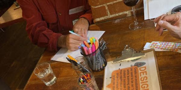 event participants designing logos on paper using colorful markers