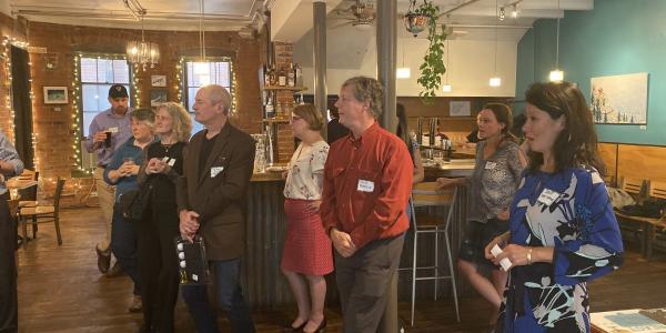Participants await announcement of door prize winners inside Cafe Aion