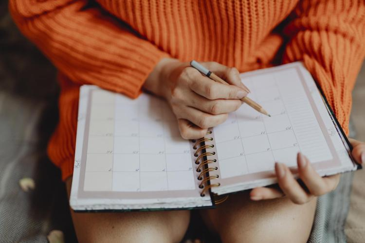 Young woman marking a date in her day planner