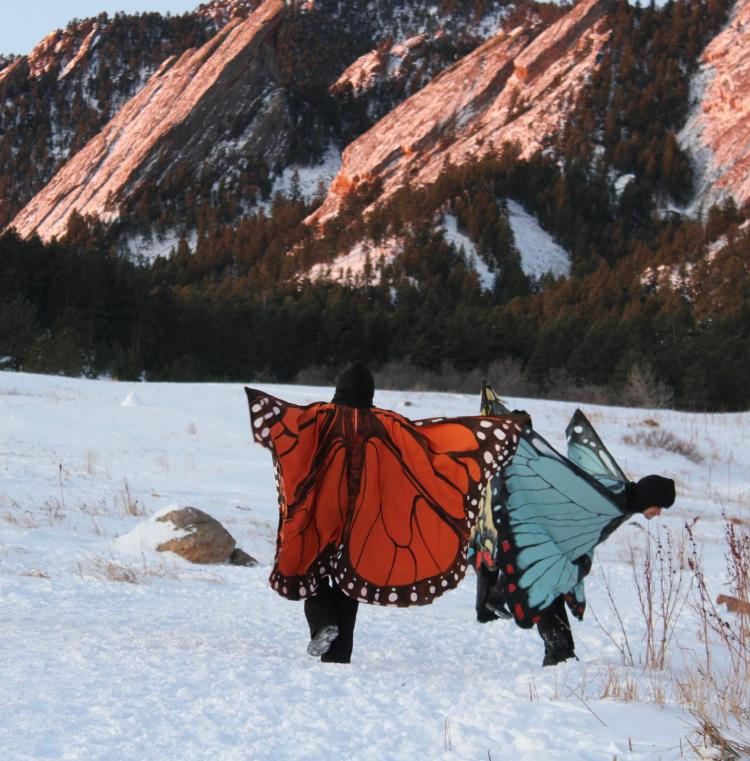 Emmet Norris, costumed as a blue morpho butterfly, in front of the Boulder Flatirons with a student dressed as a monarch butterfly