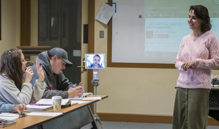 Students chatting with their instructor. One of the students appears on-screen on a Kubi device.