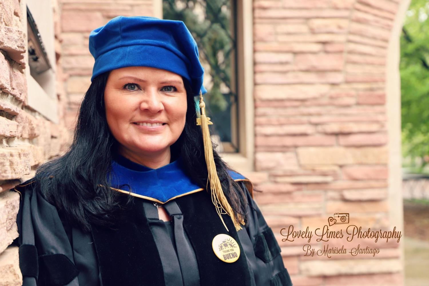 Clara Smith in doctoral regalia in front of the CU Boulder School of Education