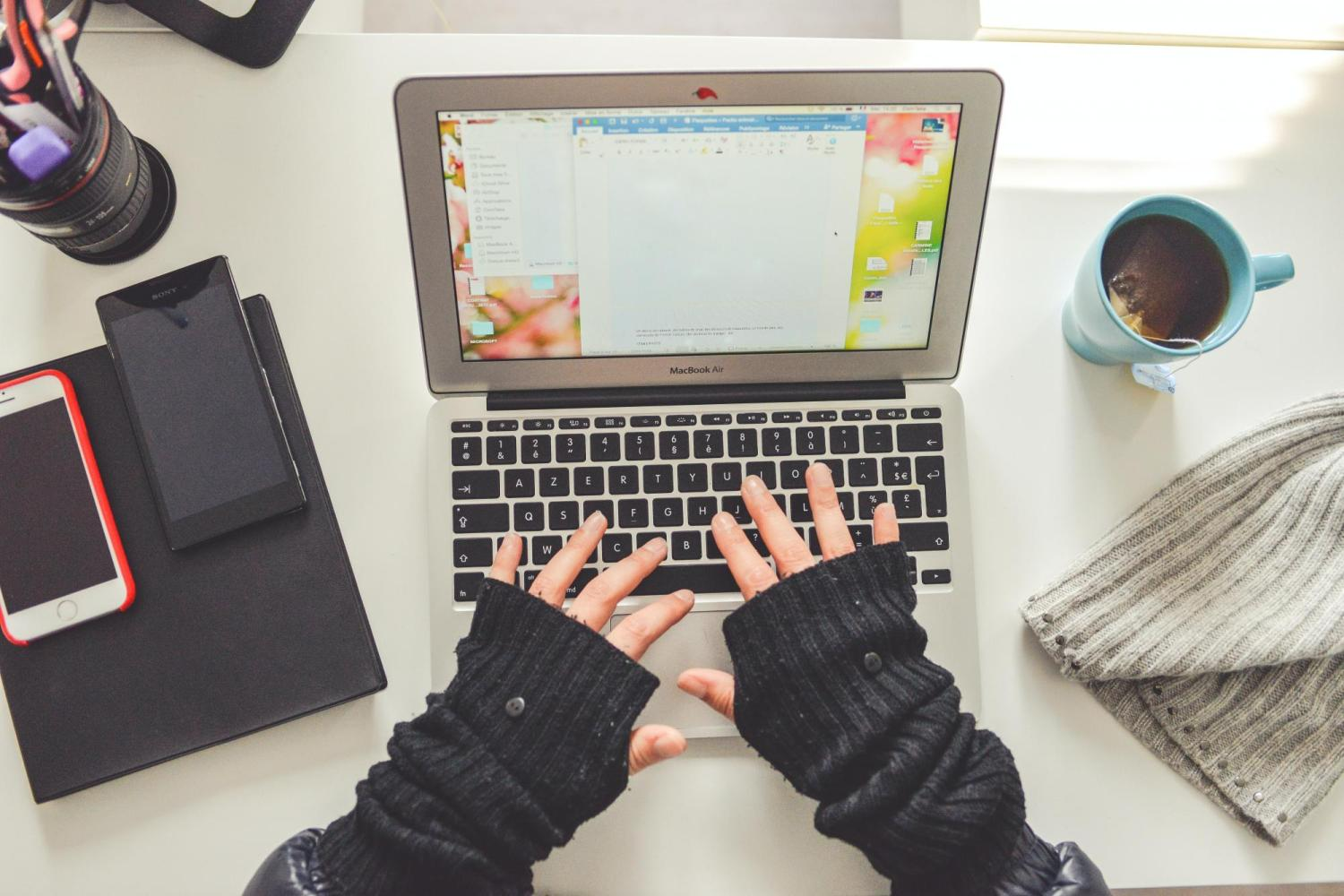 Gloved hands using a laptop next to woolen cap and hot beverage