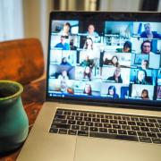 Coffee mug next to a laptop displaying participants in a Zoom meeting