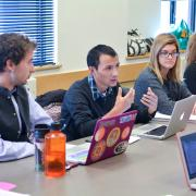 Students with laptops at a conference table