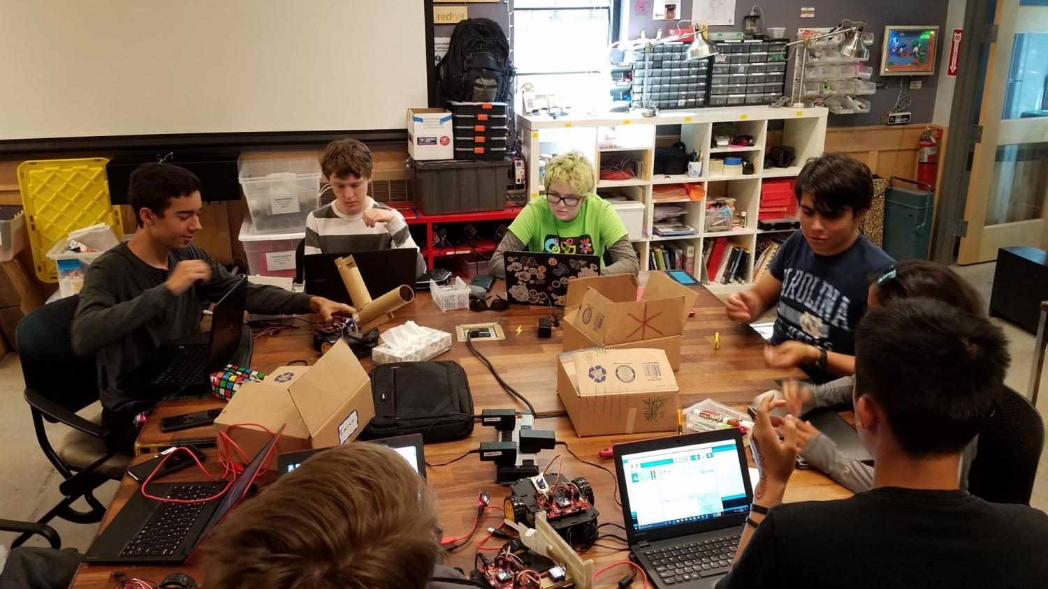 Members of CU Science Discovery Robotics Engineering Academy sit around a table.