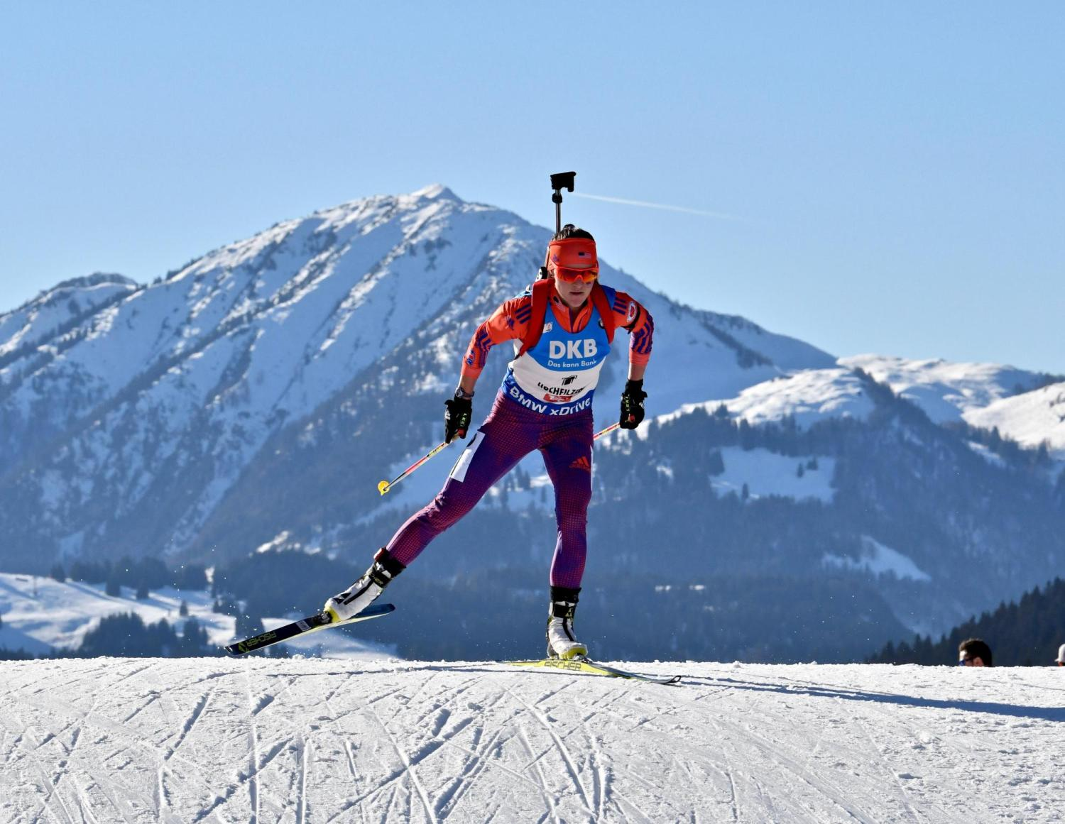 Joanne Reid skiing with a rifle on her back