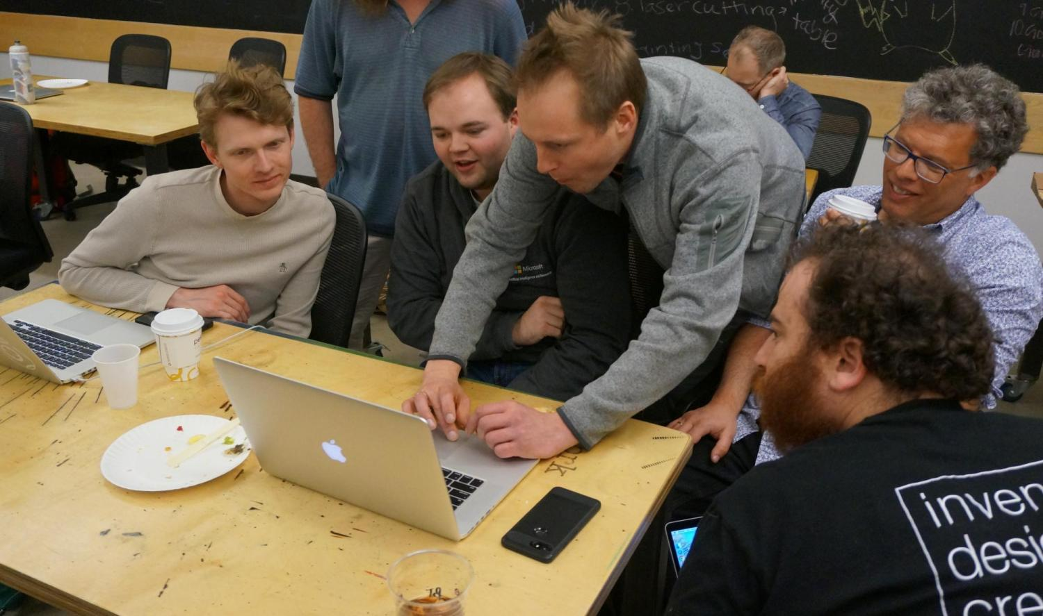 Tom Ball demonstrates MakeCode on his computer,  surrounded by workshop participants.