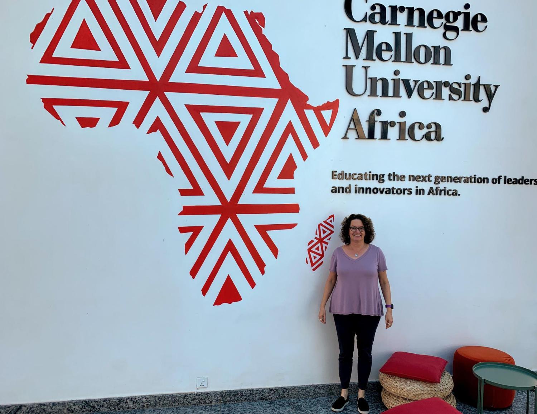Aileen Pierce stands next to a CMU Africa sign.