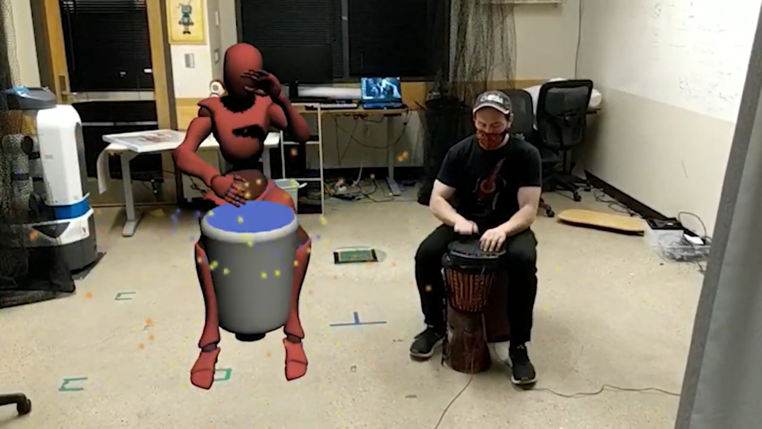 Torin Hopkins beats on a drum next to an avatar also beating on a drum.