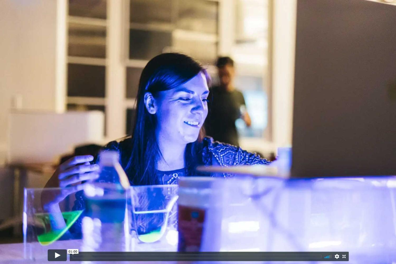 woman bathed in blue light with lab equipment