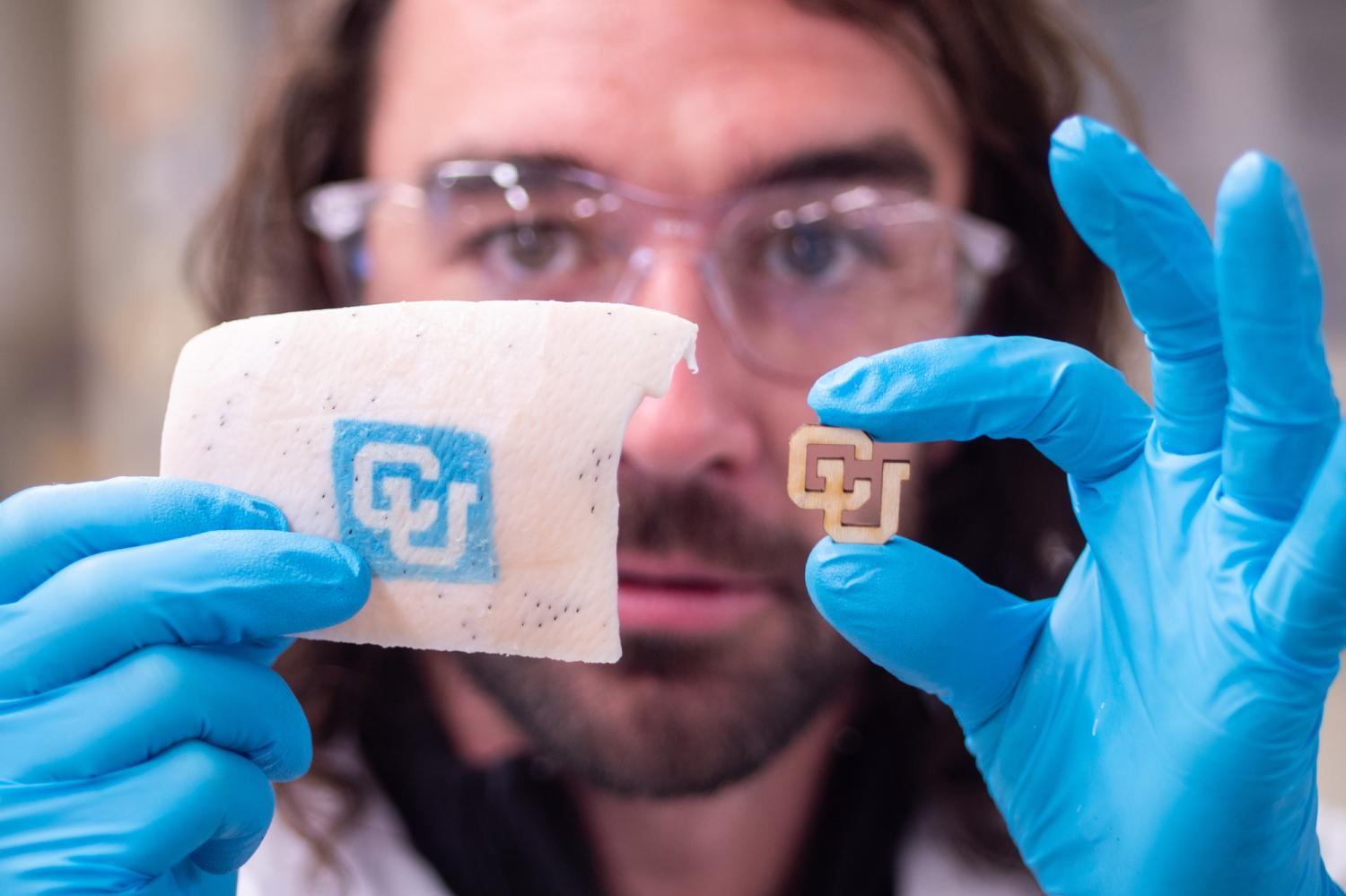 Carson Bruns, holds his gloved hands forward and holds a CU logo and a piece of pig's skin with the logo that covered the pigskin leaving CU without color and the rest of the exposed pig skin in blue ink, thereby making it possible to read the CU logo.