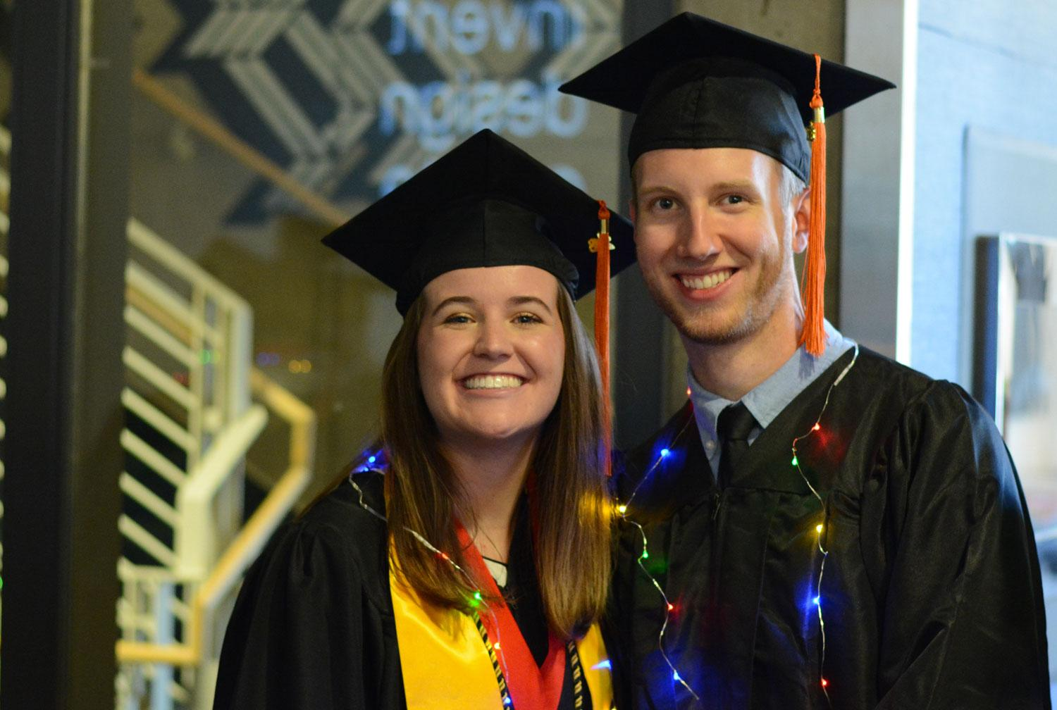 Two students pose before graduation ceremonies.