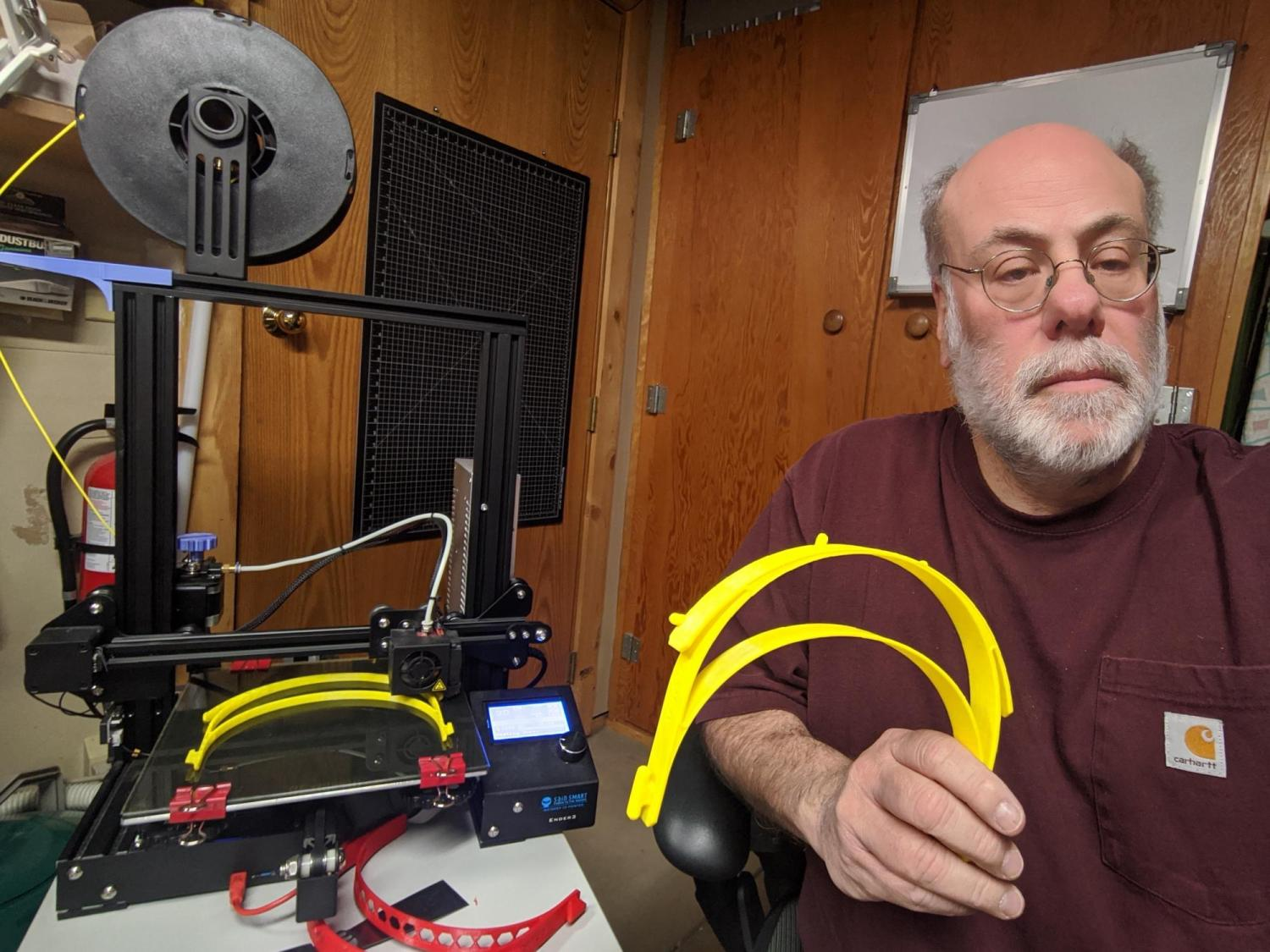 Wayne Seltzer holds shield parts made on his 3D printer next to the printer.
