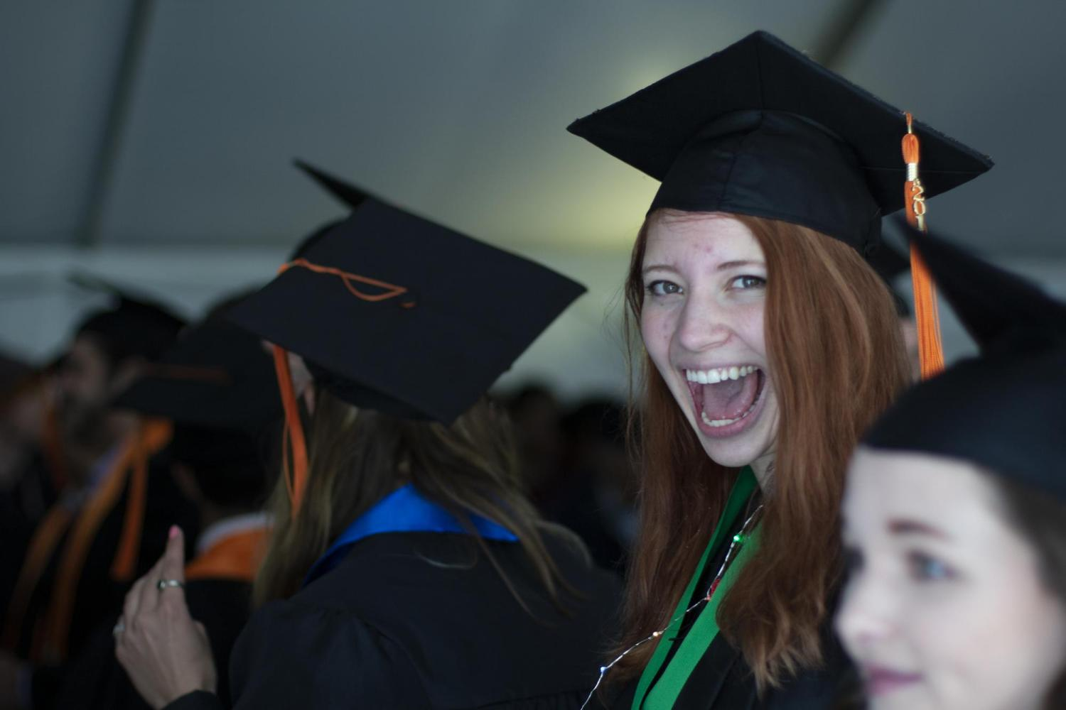 Delaney Winkler in cap and gown smiles while waiting to get her diploma.
