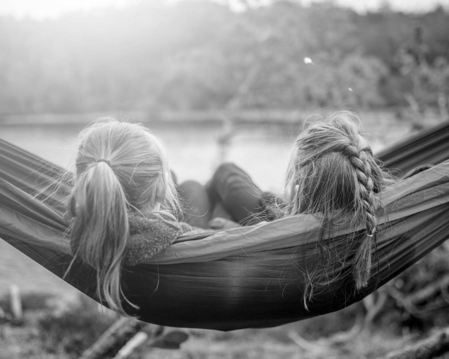 Back of two adolescent girls heads swinging in a hammock by a lake.
