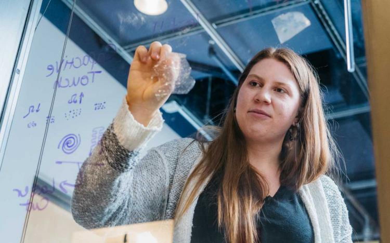 Fiona Bell peels bioplastic from window.