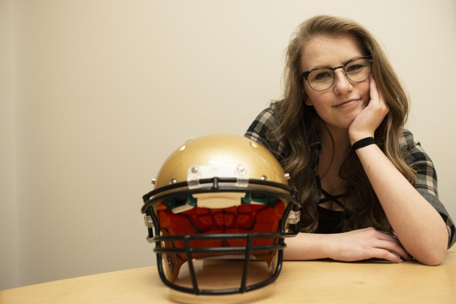 Kailey Epp sits next to a football helmet.