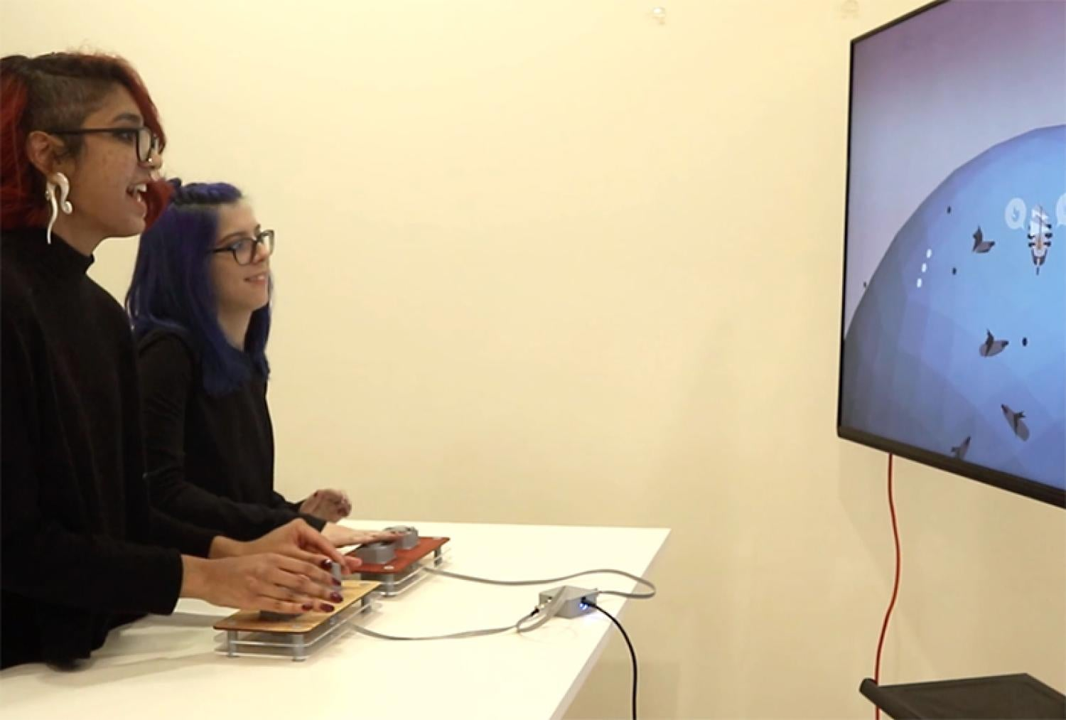 Two women play multi-controller video game
