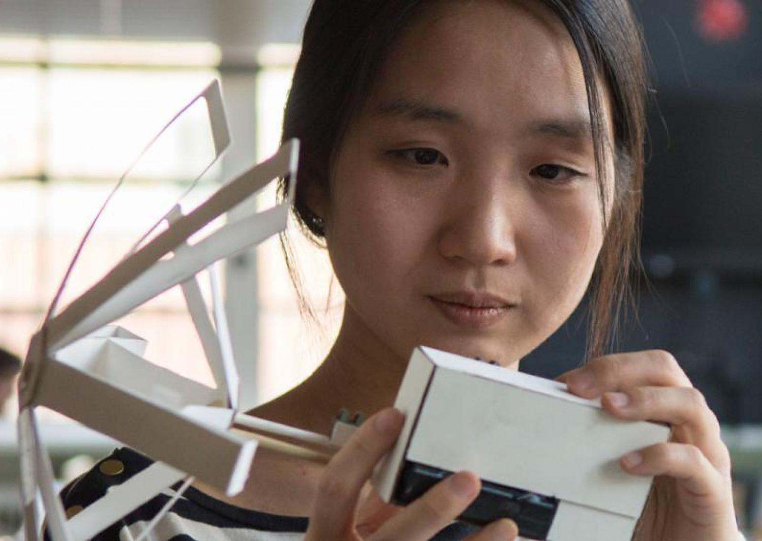 HyunJoo Oh works with mechanical paper devices.