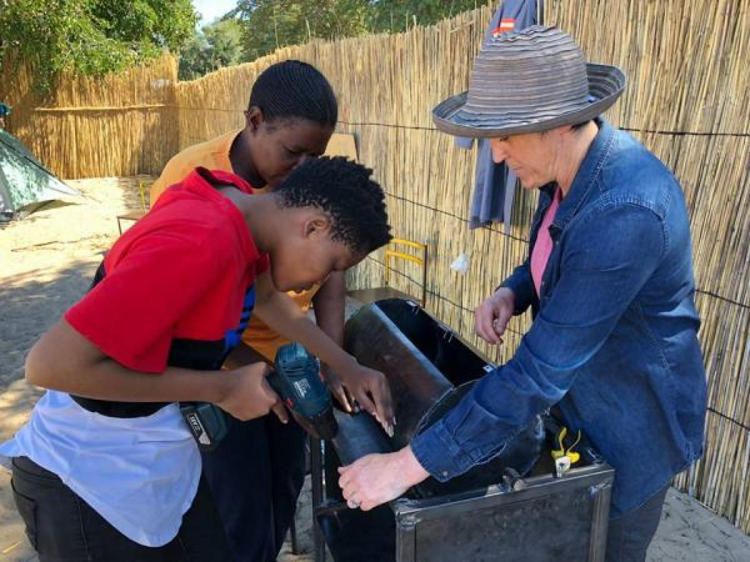 Kari Santos working with two youths to build peanut roaster