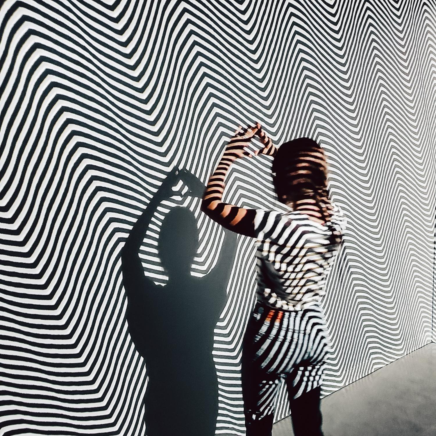 Woman with her back to the camera  stands in front of the projected black and whit4e stripes in the Moire Room