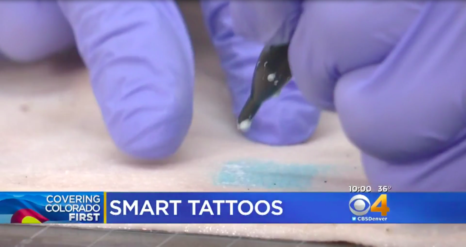 Screenshot of CBS video of gloved hands tattooing on pig skin